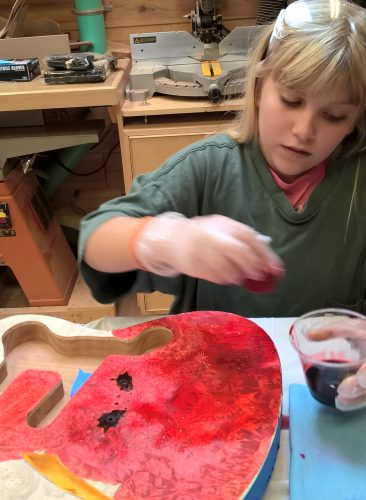 Shop helper applying base coat of red dye stain.